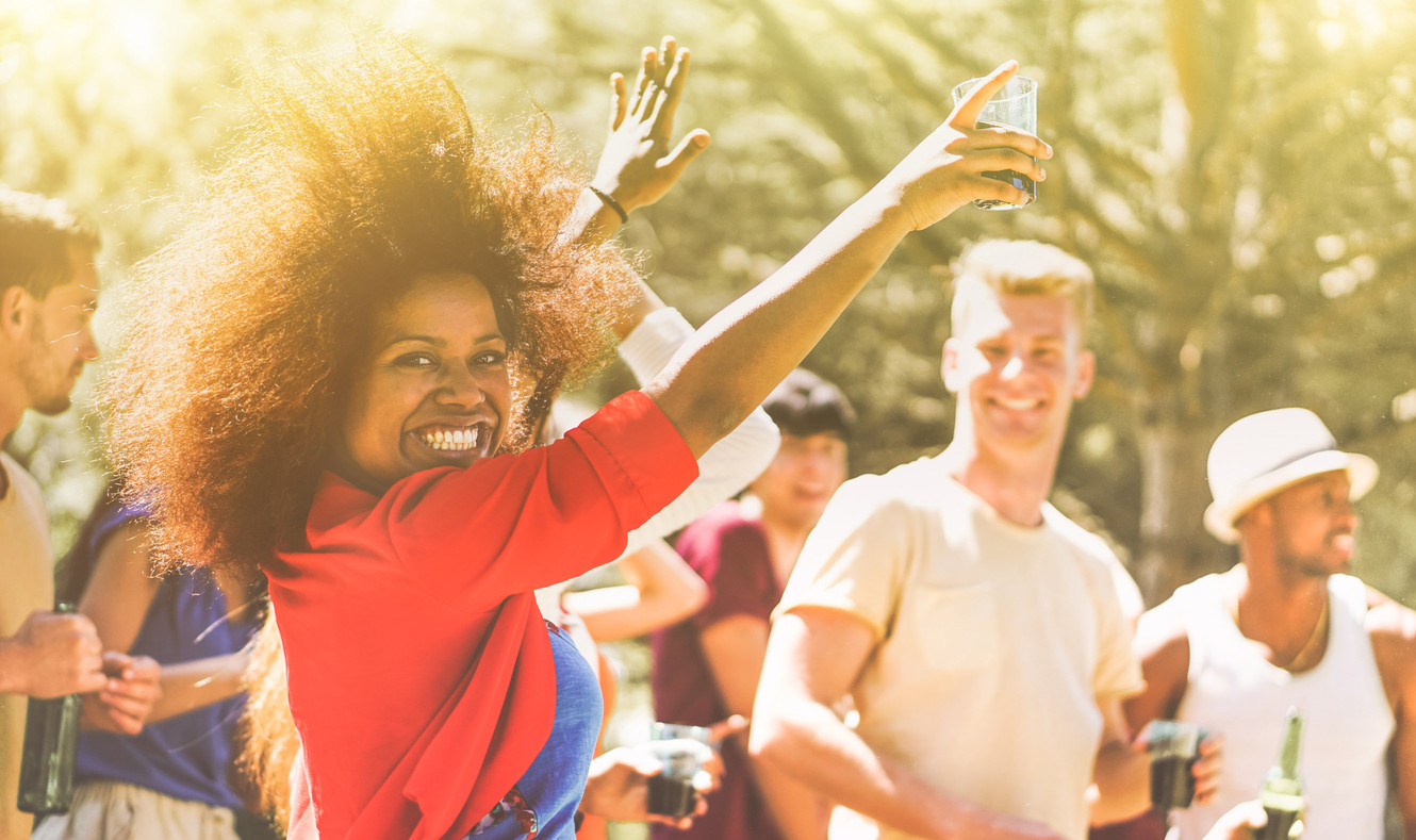 Young people dancing in forest party on summer time - Happy friends drinking cocktails and laughing together outdoor in music festival - Focus on black girl face - Youth lifestyle and event concept